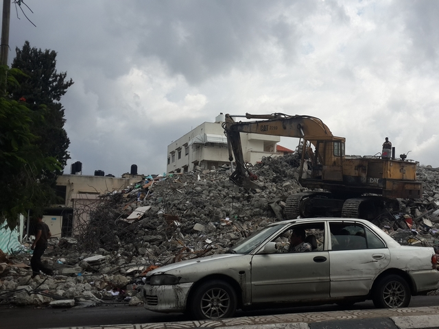 A car in front of building that have been destroyed and rubble that may contain explosive weapons. Gaza.