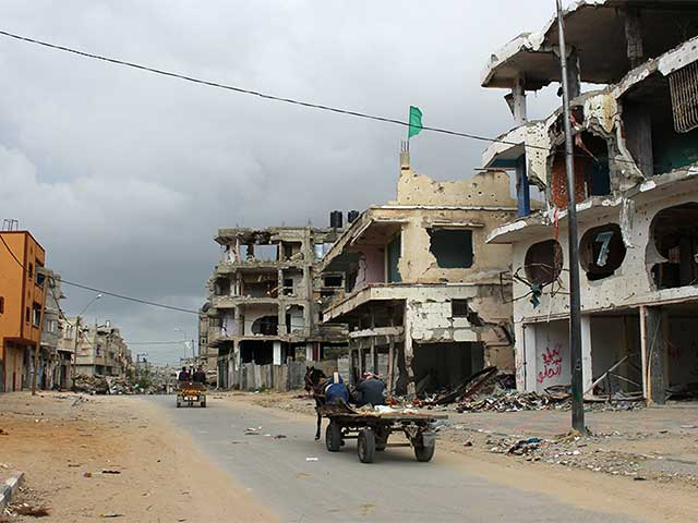 People on horse and cart pass buildings in Shejaiya, Gaza. The area is heavily contaminated with ERW and many people are still living amongst the rubble.