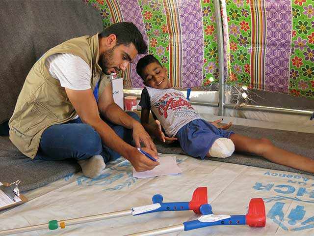 Physio Mohammad with Adbel Rahman, who lost his leg in a bombing, Mosul.