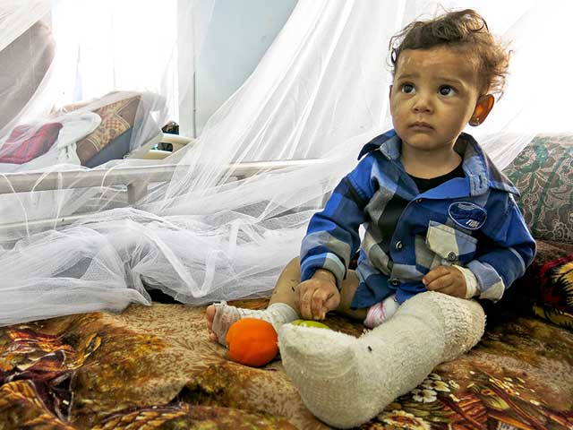 One-year-old Ali sitting in his hospital bed.