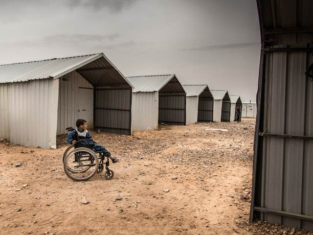 A disabled Syrian child sitting in a wheelchair in Azraq camp, Jordan.
