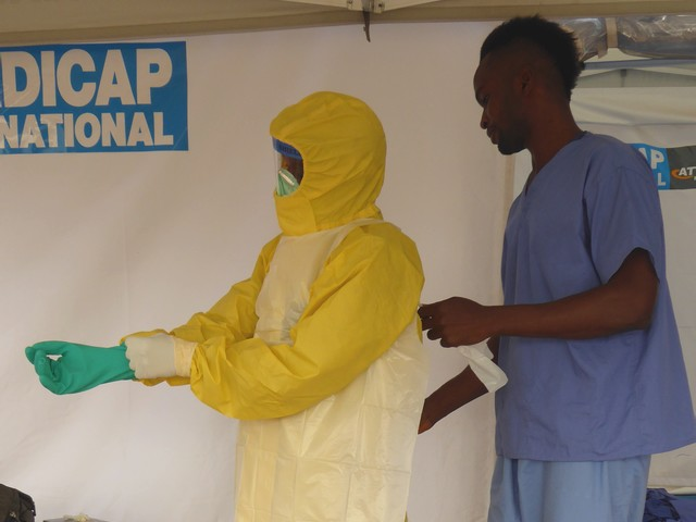 Members of Handicap International's ambulance service team cleans an ambulance with a chlorine solution. Sierra Leone.