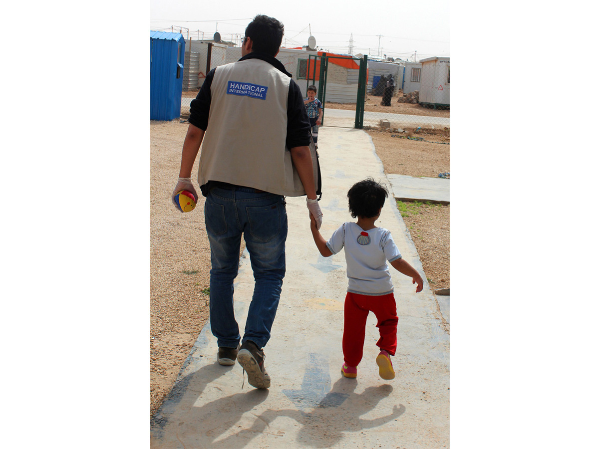 Malak, 5, goes outside with physiotherapist Mohammed