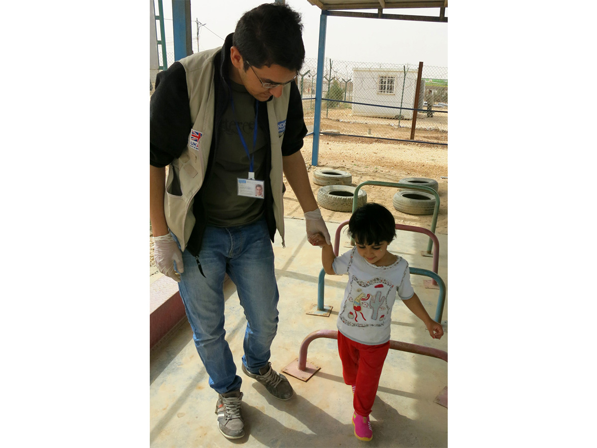 Malak, 5, walking with physiotherapist Mohammed