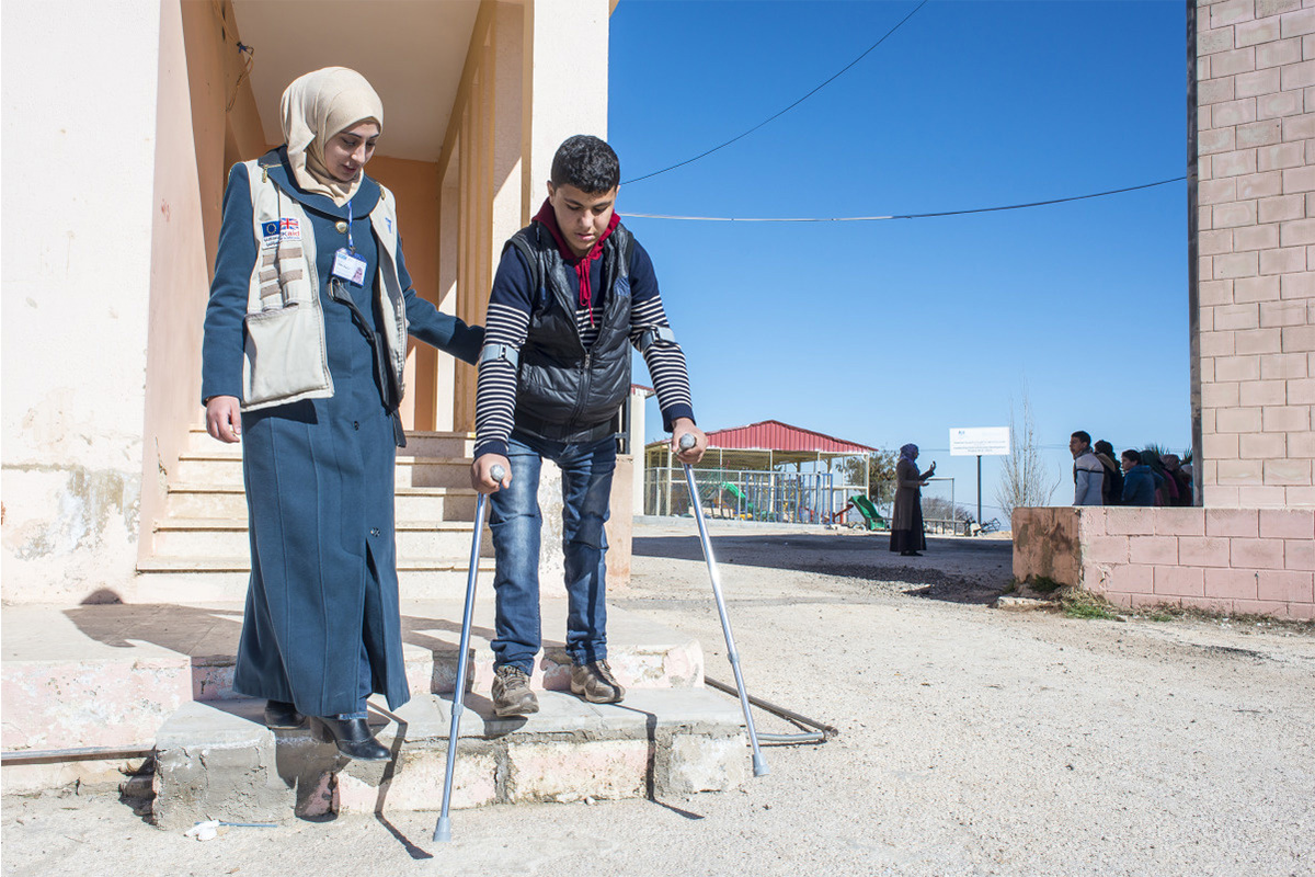 Qusay steps outside with Salam, his physiotherapist