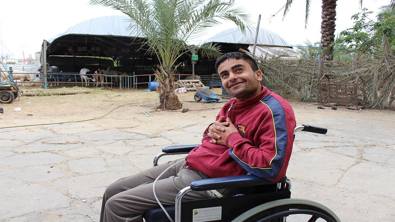 Odai outside in the yard, with the family farm behind him. Gaza.