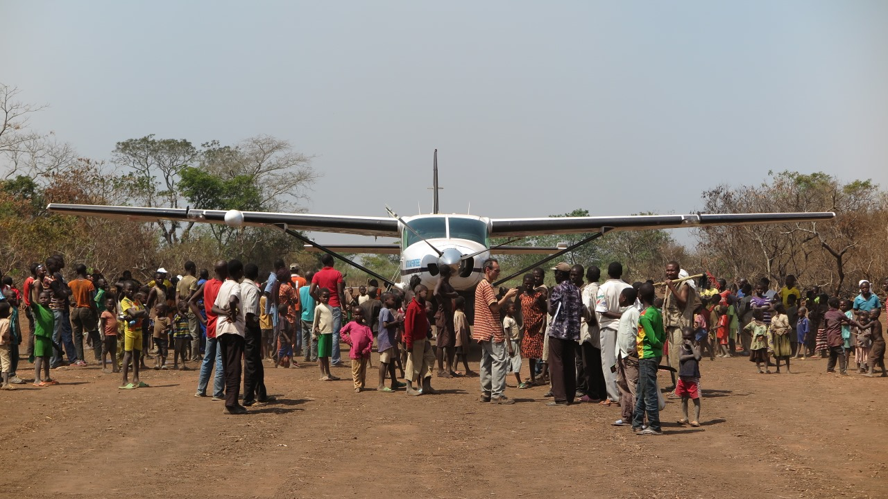 Inhabitants of Sibut greet the first aeroplane to land on the airstrip since its rehabilitation.
