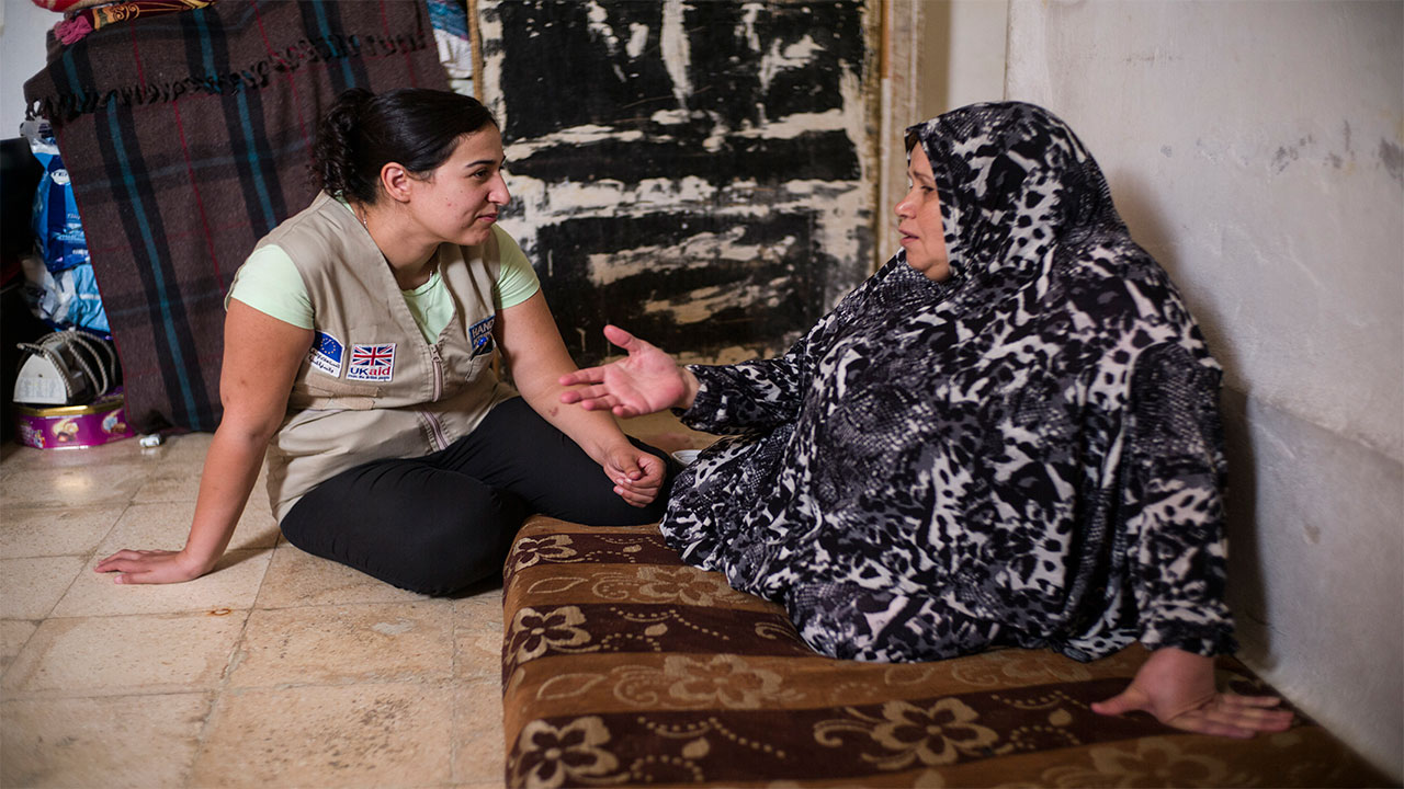 Ala'a with Aida, whose husband, Hassan, is receiving rehabilitation  care from Handicap International's team after several strokes left him partially paralysed. Jordan.