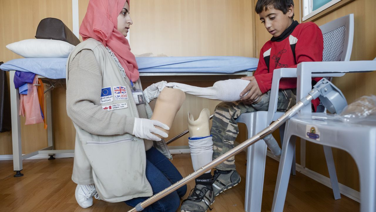 Mohamad, 12, lost his left leg after a bombing in Syria. Now living in Azraq refugee camp in Jordan, Mohamad has been fitted with a prosthesis and is seen here during a rehabilitation session with Handicap International physiotherapist Asala.