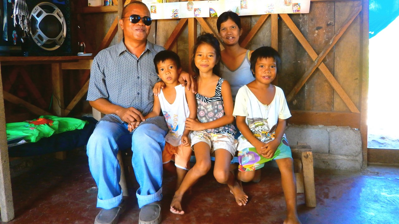 Renato, his wife and three of their six children in their newly repaired home. The Philippines.