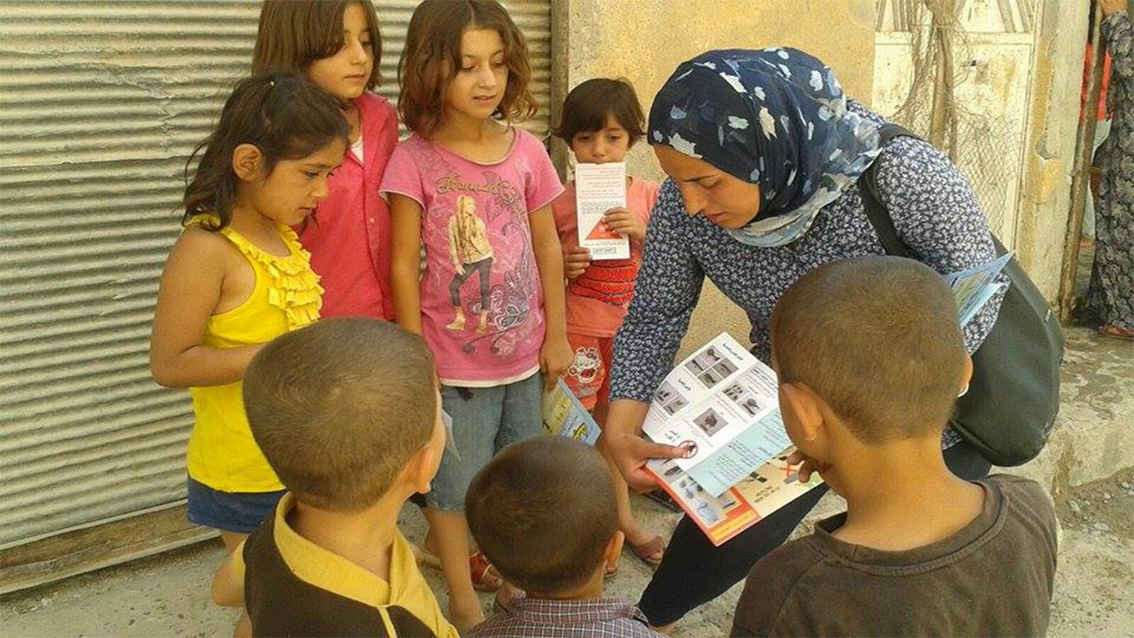 Leaflets are distributed to children in Kobani as part of Handicap International's  risk education activities.