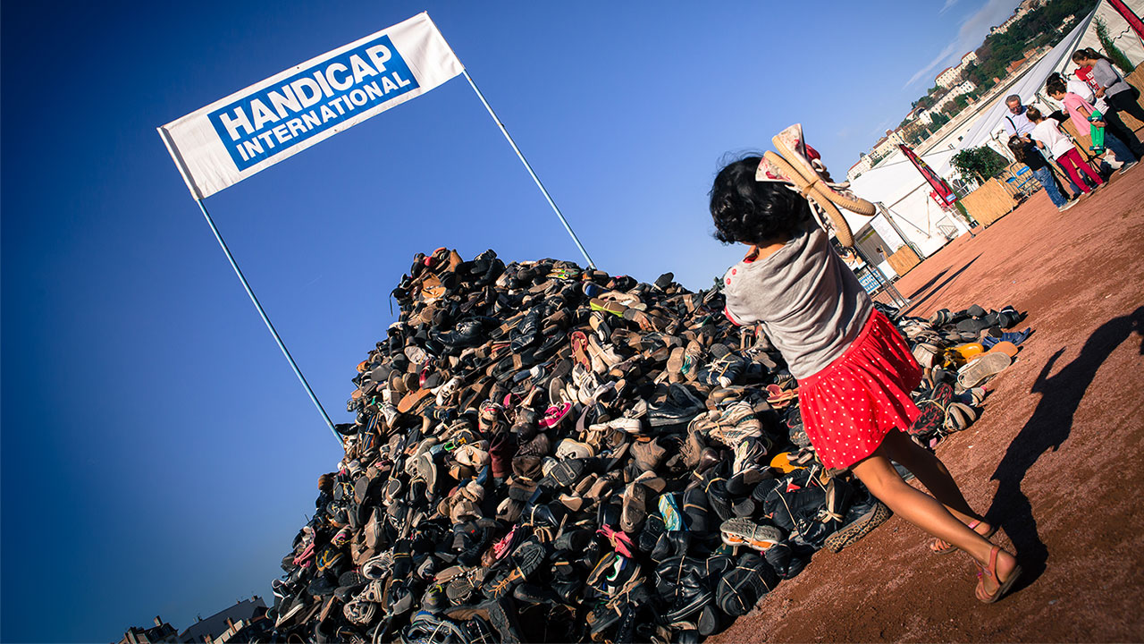 A pyramid of shoes, each shoe represents a life or limb lost to a landmine or cluster bomb