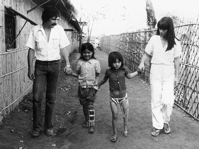 Jean Baptiste and Marie Richardier with two children, Mom and Sorpin, in the Khao I Dang refugee camp on the Thai-Cambodia border, 1980s