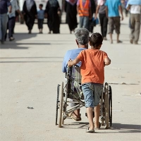 A child pushes a man in a wheelchair in Zaatari refugee camp, northern Jordan.
