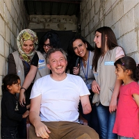 Giles Duley with Bana (left), her sister, and the Handicap International rehabilitation team in Lebanon.