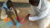 A child with his father doing puzzle during a psychomotor development session in the Dadaab camp, Kenya