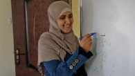 Ashwaq, wirting on a white board in the centre that she founded, Jordan.
