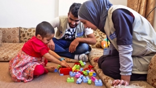 Huda plays with Handicap International staff Abood and Salam as part of a rehabilitation session.