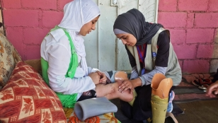 Salam has her legs checked by a Handicap International physiotherapist