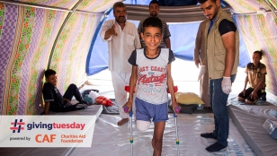 Abdel Rahman stands with crutches in his tent, while HI physiotherapist Mohammed looks on.