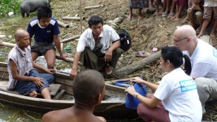 Eric Weerts and the Handicap International team conduct a situation assessment for a person with disabilities who needs to use a boat to reach his home from the road due to the floods. Myanmar