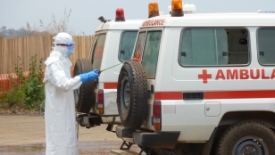 A member of Handicap International's ambulance service team cleans an ambulance with a chlorine solution. Sierra Leone.