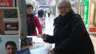 A Christmas shopper in Rugby takes time out to sign the Stop Bombing Civilians petition at a stall organised by Rugby Soroptimists.
