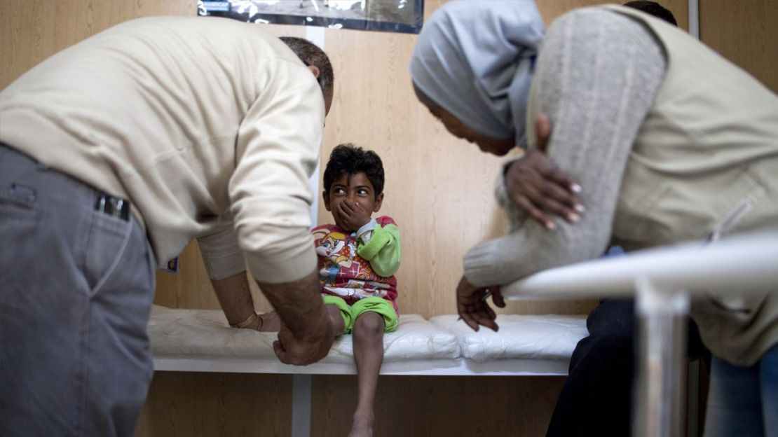 A Handicap International physiotherapist examines Qasem, a 10-year-old Syrian girl with dwarfism, Jordan.
