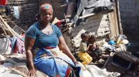 Lucia in front of the remains of her home, destroyed by Cyclone Idai, Beira, Mozambique; }}