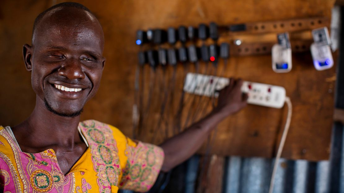 Ali charges phones in the shop he owns with his wife Abiba, in Kakuma Town, Kenya. Both Ali and Abiba are blind. They are from Kakuma and have received support for their shop from Humanity & Inclusion and other NGOs after NGO's arrived to support the influx of refugees.