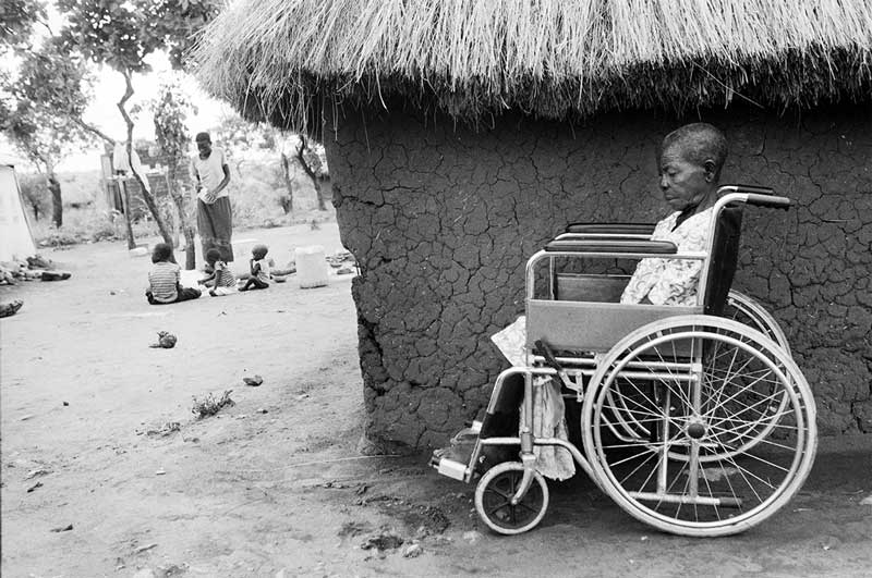 Catarina sitting outside a hut in her wheelchair.