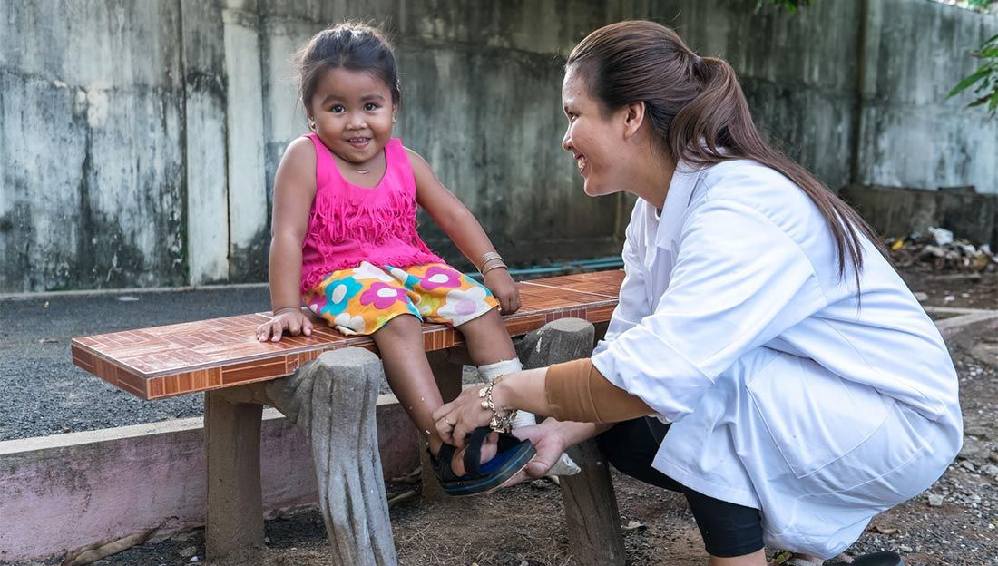 Phaly Heang, 4, having a rehabilitation session with Ratha Mom at HI's rehabilitation centre in Kampong Cham.