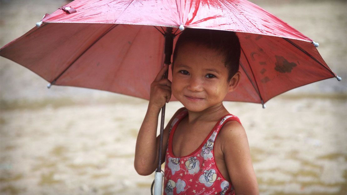 A child with an umbrella in Mae La refugee camp.