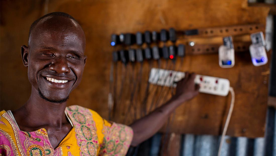 Ali, who is blind, charges phones in the shop he owns with his wife Abiba, who is also blind, in Kakuma Town, Kenya. Both Ali and Abiba are from Kakuma and have received support for their shop from Humanity & Inclusion.