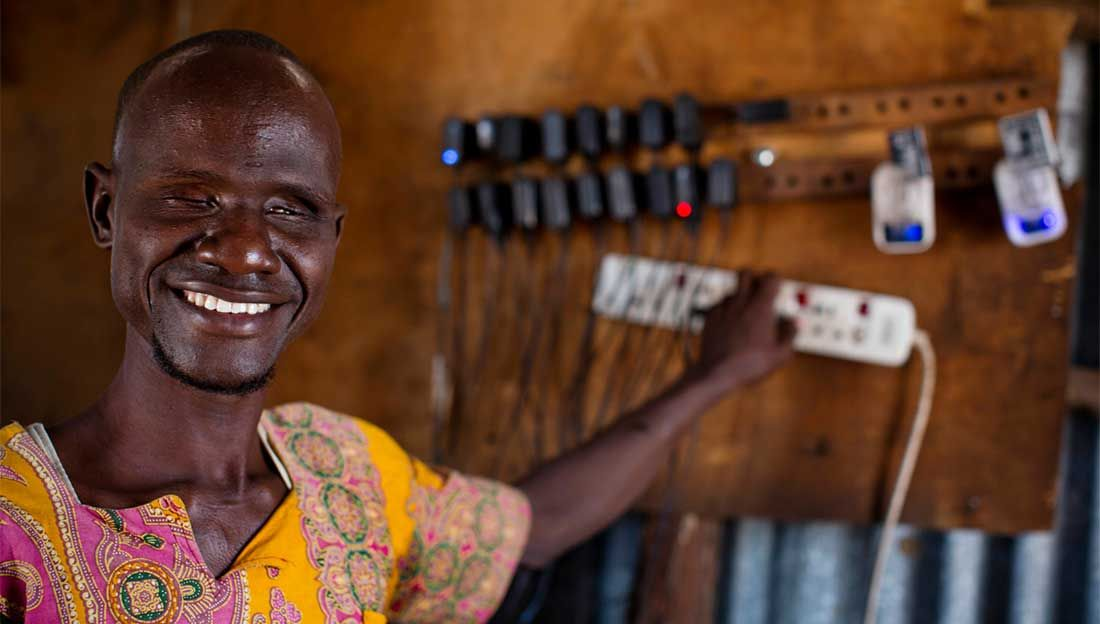 Ali, who is blind, charges phones in the shop he owns with his wife Abiba, who is also blind, in Kakuma Town, Kenya.