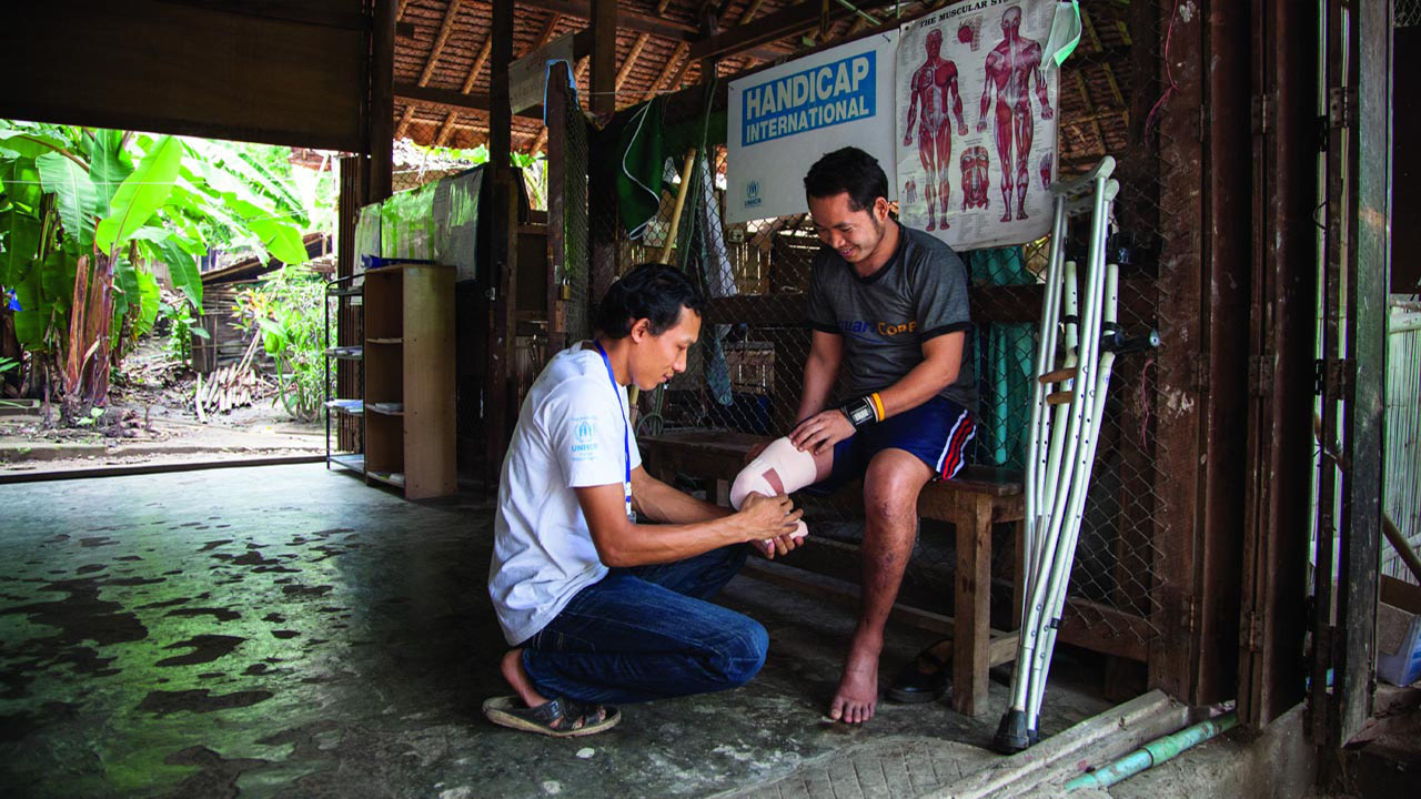 Supporting an amputee, Thailand - Handicap International