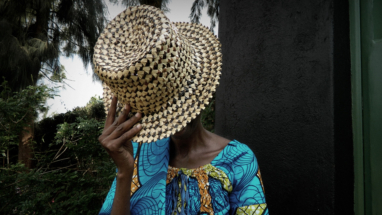 A woman with her face hidden by a hat.; }}