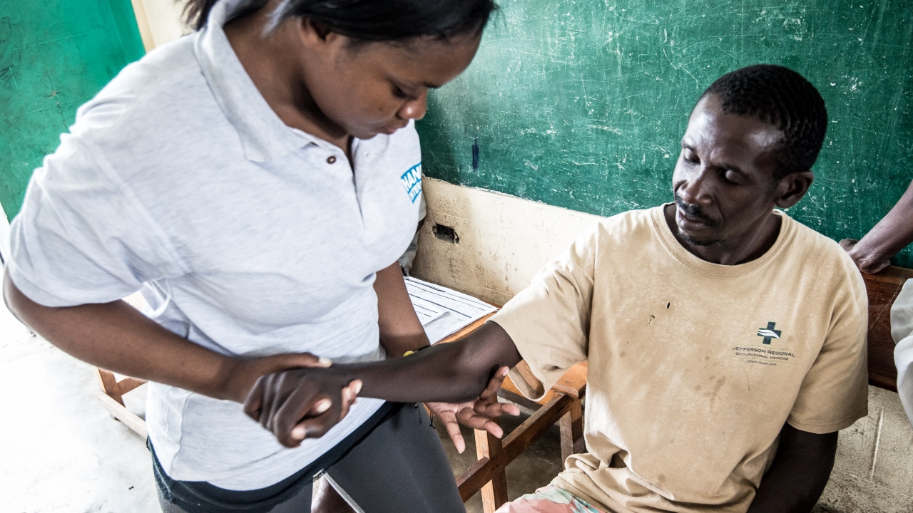 A man with hemiplegia receiving rehabilitation care from a Handicap International physiotherapist, Haiti.; }}