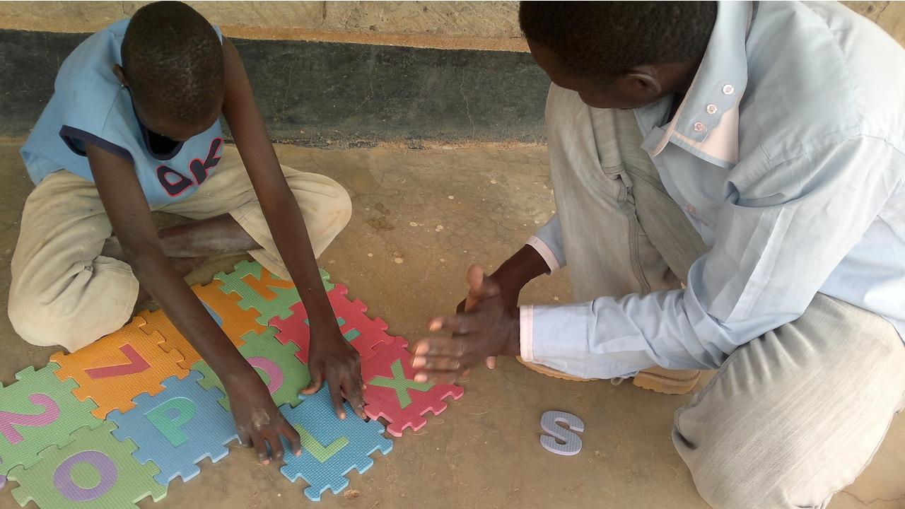 A child with his father doing puzzle during a psychomotor development session in the Dadaab camp, Kenya; }}