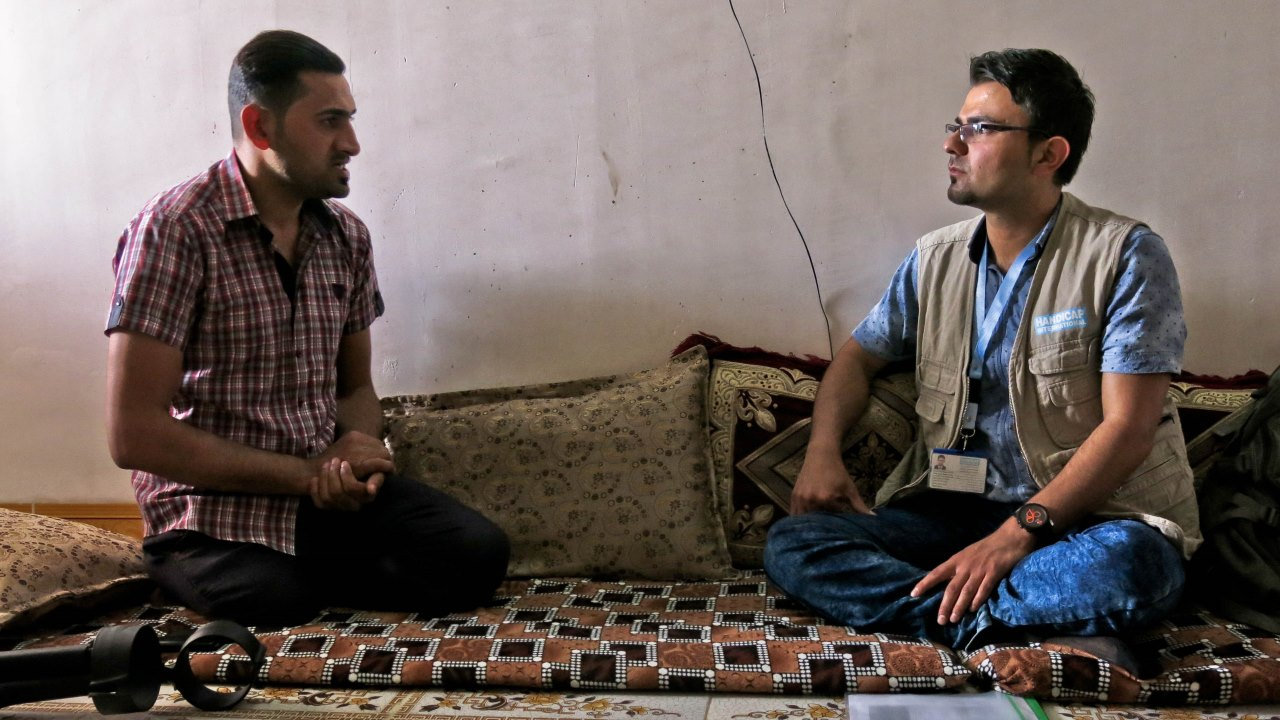Shwan, a member of Handicap International's team, listens to Abdelillah during a psychosocial support session.
