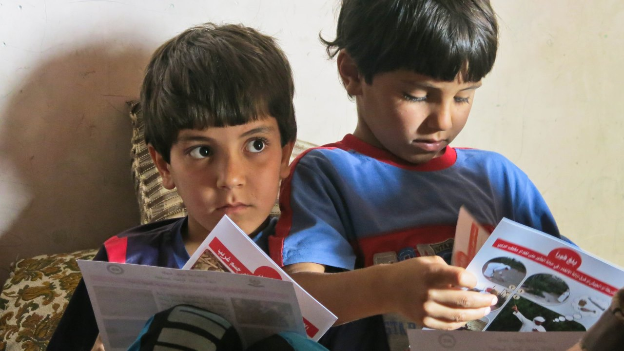 Two brothers look at the leaflets left by Handicap International's team, at the end of a session.