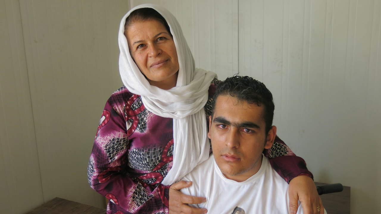 Badria and her son at a meeting organised as part of a capacity-building project for Syrians with disabilities and injuries.