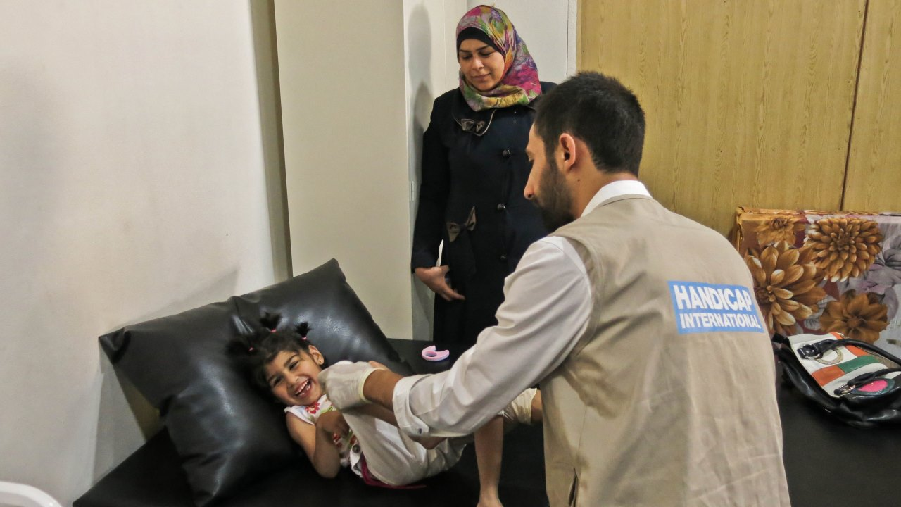 Dari watches as her daughter, Afra, receives physiotherapy care.