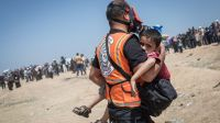 A medic carrying a child to an ambulance after inhaling tear gas, on 14th May 2018 in Gaza City. ; }}