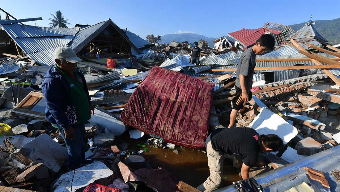 Indonesian men search for a family member at their damaged house in the Balaroa village in Palu, on October 1st, 2018, after an earthquake and tsunami hit Indonesia on September 28th.