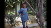 Sanaullah, 5, standing next to a tree wearing his prosthetic leg from HI. He lost his leg to a mortar in Afghanistan.; }}