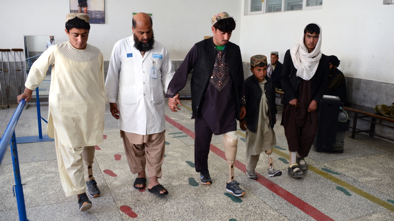 A physiotherapist from Kandahar Physical Rehabilitation Centre guiding the amputees during gait training process.