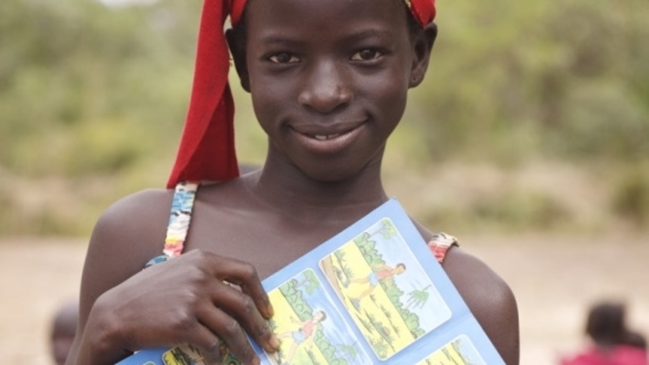 Having just attended an awareness raising session, 11-year-old, Awo Goudiaby holds up a leaflet with drawings depicted important safety messages. Senegal.