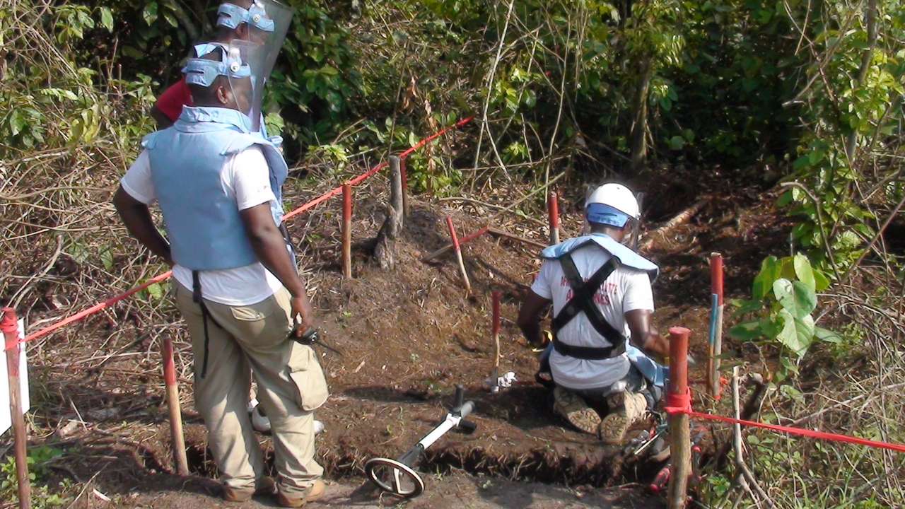 Handicap International deminers in action near Kisangani, DRC.; }}