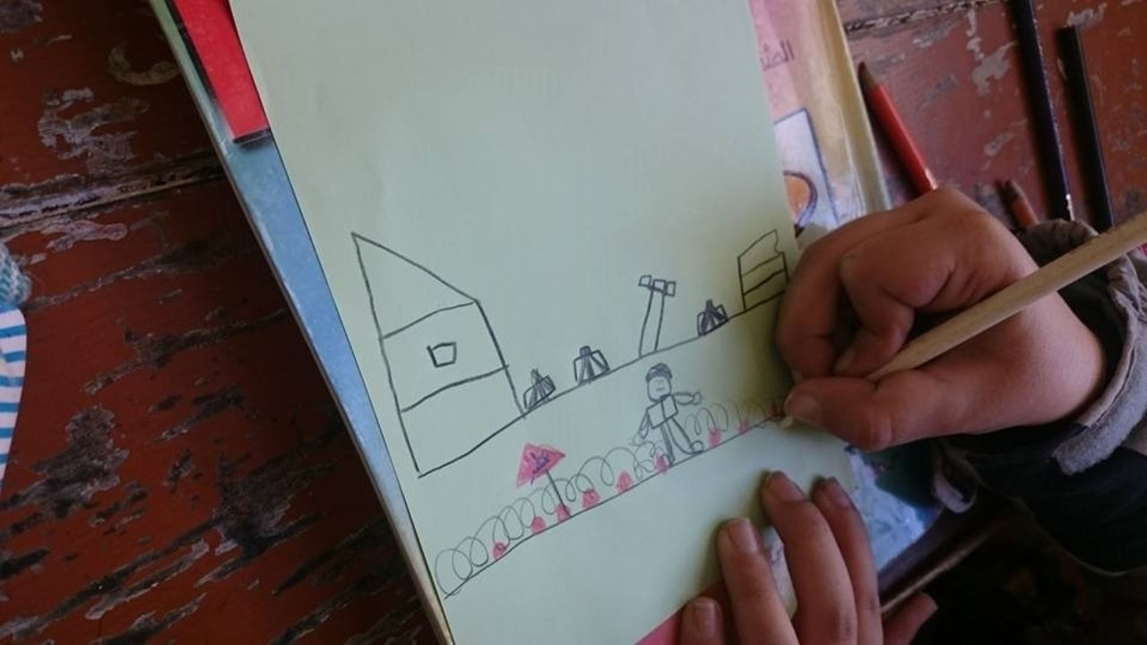 A child drawing an area contaminated by mines and explosive remnants of war during an awareness-raising session. ; }}